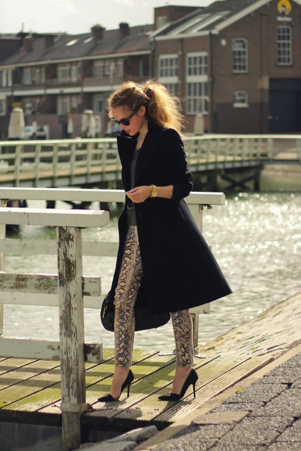 With knee-length black coat and pumps