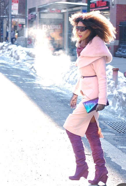 With light pink coat and metallic clutch