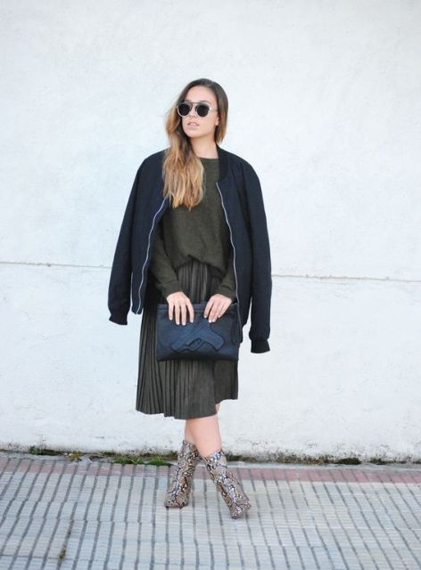 With olive green shirt and pleated skirt