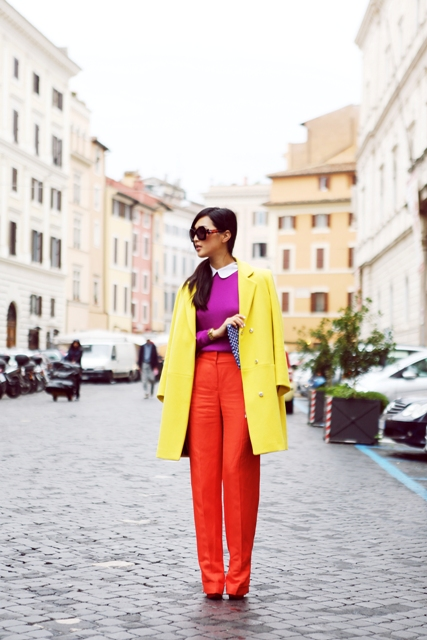 With purple shirt, red trousers and printed clutch