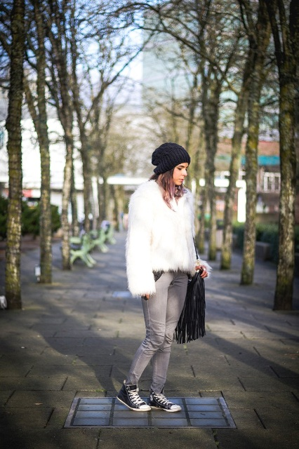 Stylish fall outfit with converse sneakers, white faux fur coat and black fringe bag