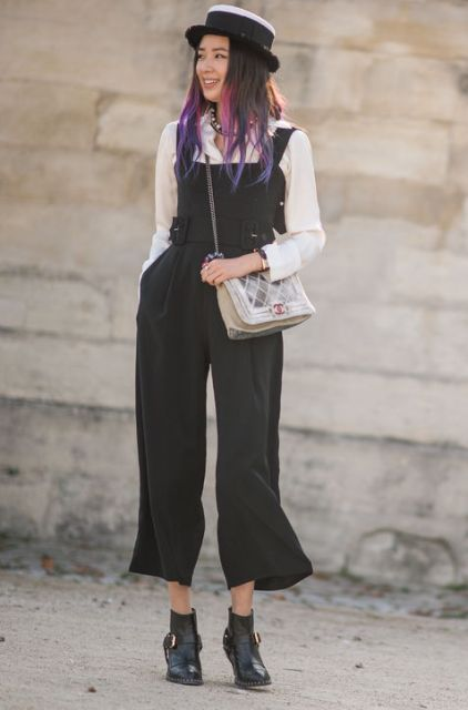 With white shirt, ankle boots, hat and crossbody bag