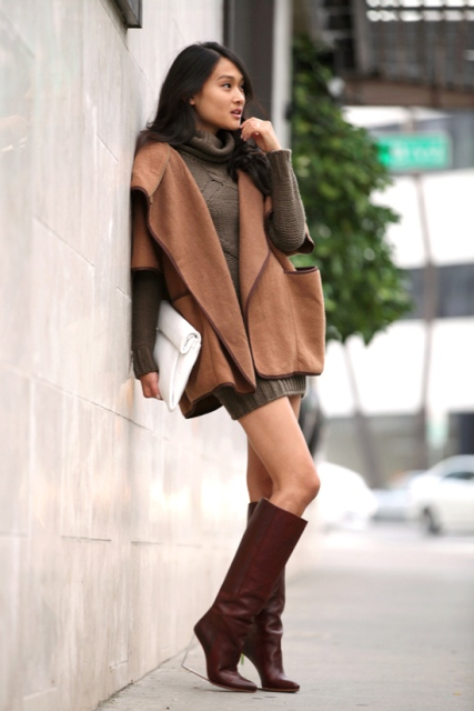 With wool cape coat, oversized sweater and white clutch