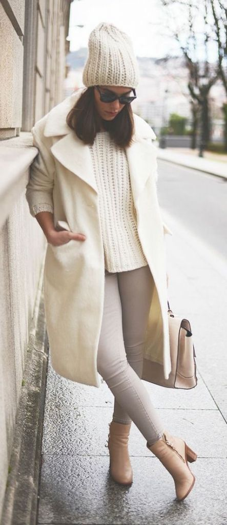 a white sweater, coat and beanie, pastel boots and a bag