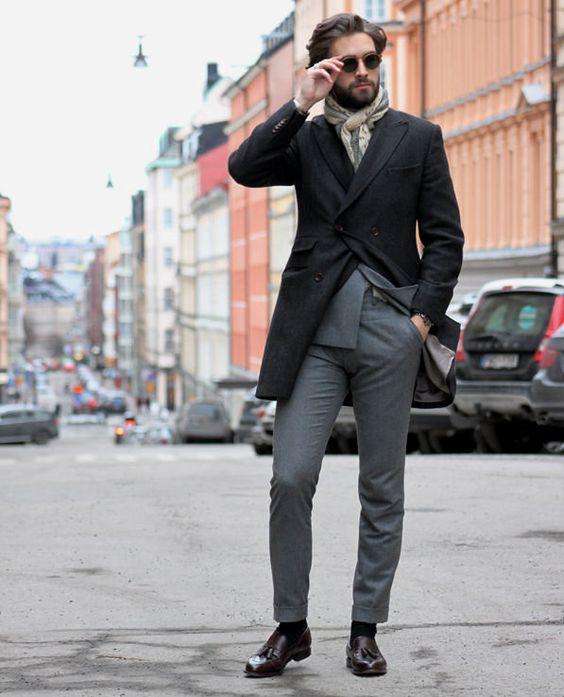 a grey suit, a black coat, a scarf
