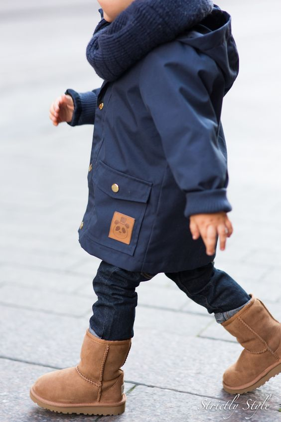 a navy coat, a navy scarf, jeans and brown leather boots