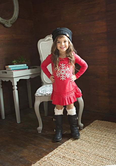 a red dress with a silver snowflake, high black boots and leg warmers and a black beanie