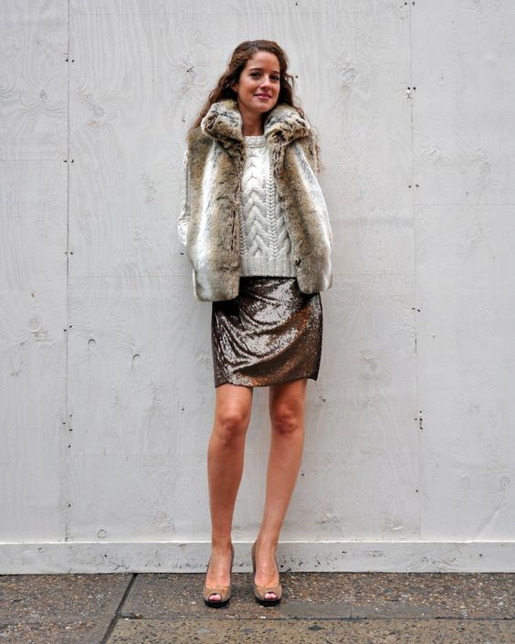 a sequin skirt, a cable knit sweater and a short fur coat over it