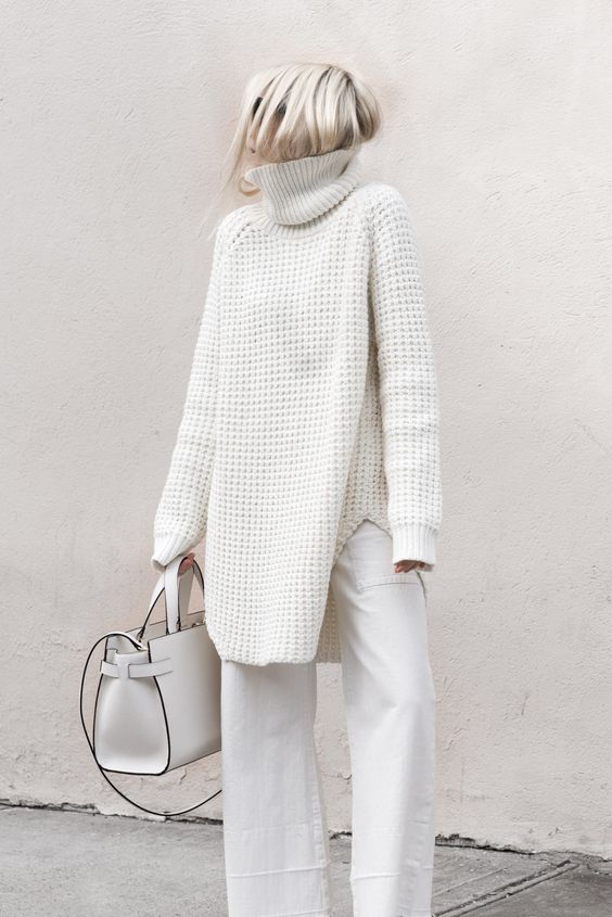 a white oversized turtleneck sweater and pants, a white bag
