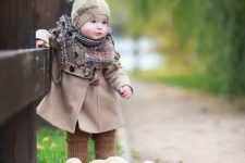 07 neutrals on – a coat and a beanie with a fur pompom, a plaid scarf and brown knit leggings