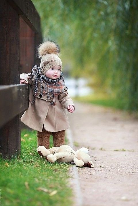 neutrals on - a coat and a beanie with a fur pompom, a plaid scarf and brown knit leggings