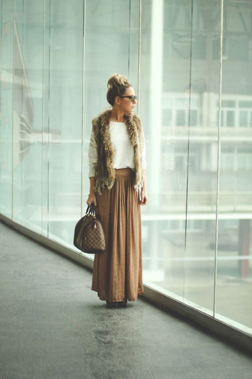 a tan maxi skirt, a white sweater and a fur vest