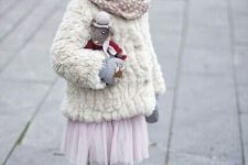 11 a faux fur coat and earmuffs, a tulle pink skirt, polka dot tights and boots