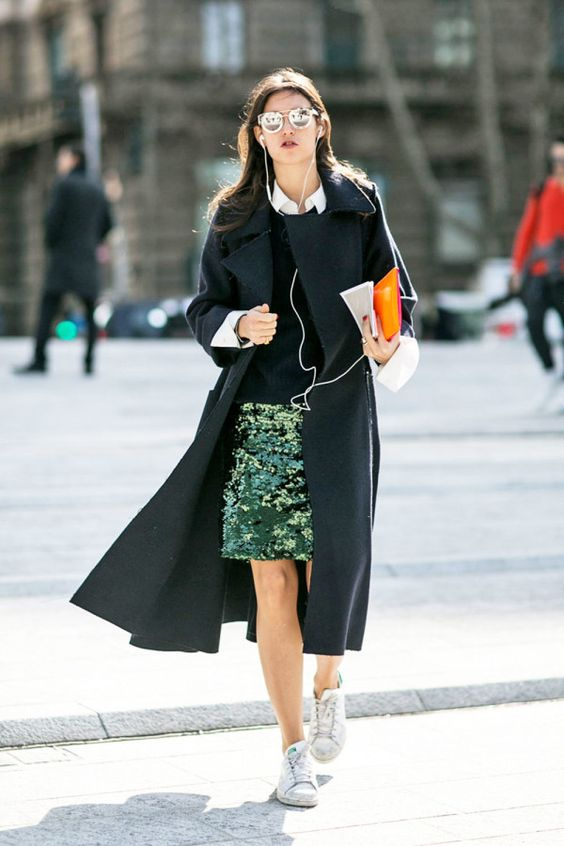 a sequined skirt is worn with a collared shirt, sweater, a duster coat, and sneaks