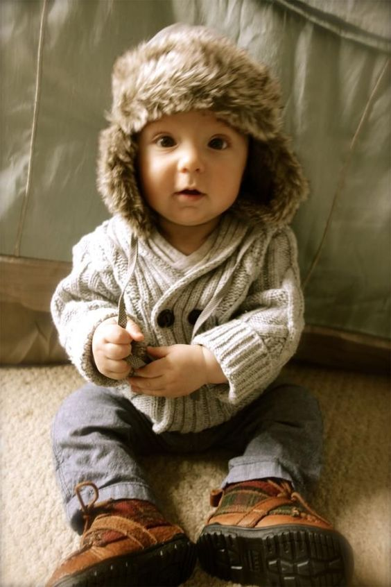 brown boots, a warm cable knit sweater, a fur hat