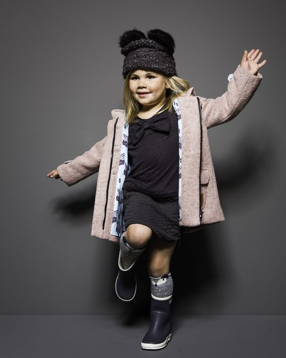 a pink coat, rain boots with leg warmers, a beanie with ears, a skirt and a jersey