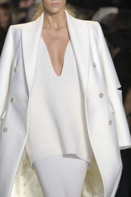 a white skirt, a plunging neckline sweater and a coat over it