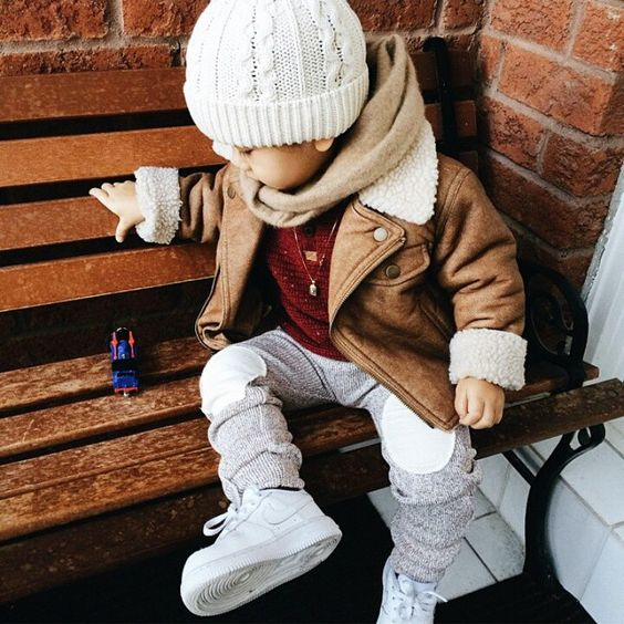 good-looking boy's outfit with grey pants, a red sweater, a brown shearling coat and a scarf, white sneakers