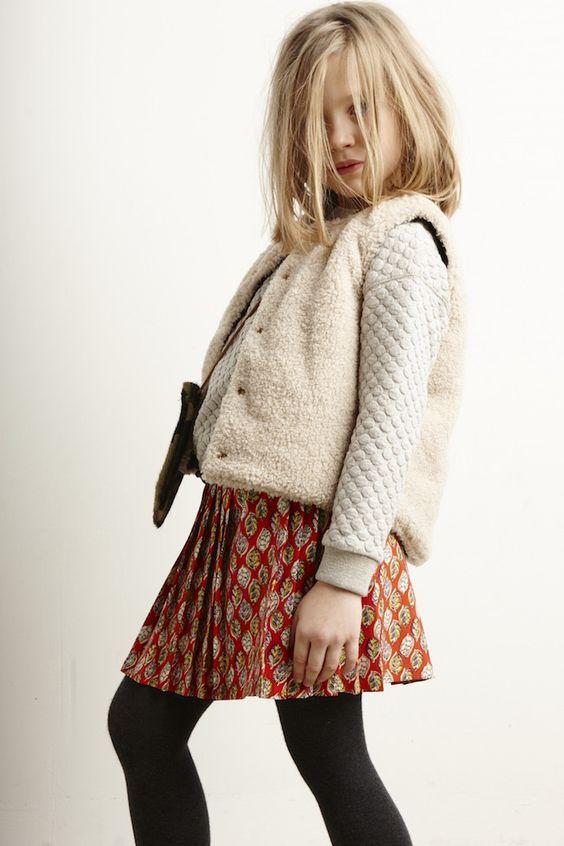 a printed skirt, black tights, a neutral jacket