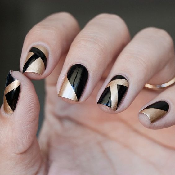 black and gold nails with geometric patterns