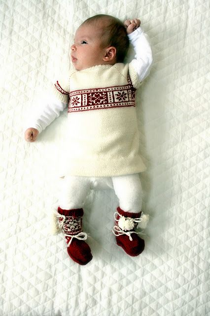 an ivory and red patterned sweater, white leggings, red socks with pompoms