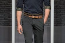 16 grey pants, a black sweater over a plaid shirt