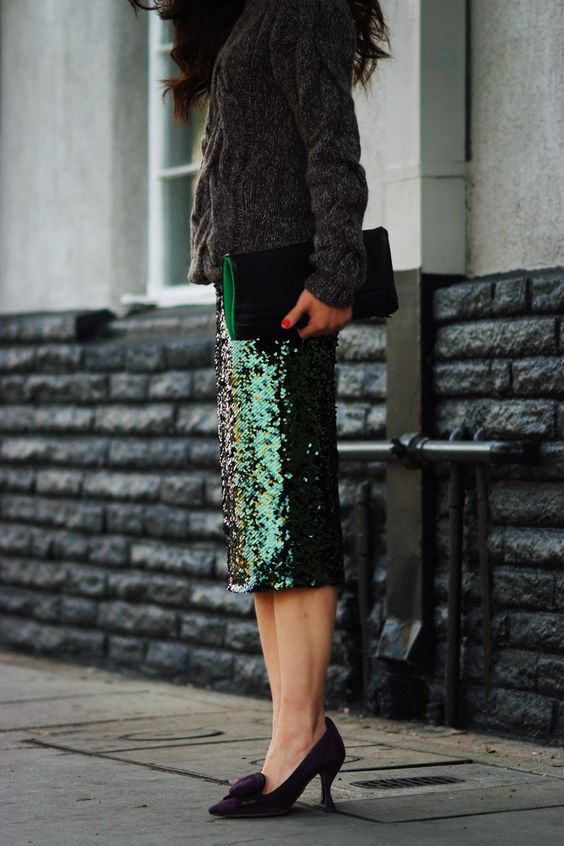 a grey chunky knit sweater, a green sequin midi and pumps