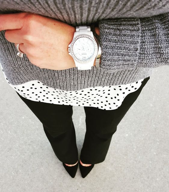 black pants, a polka dot short and a grey sweater