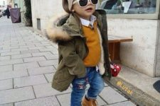 20 jeans, ocher boots and a sweater, an olive green parka and a beanie
