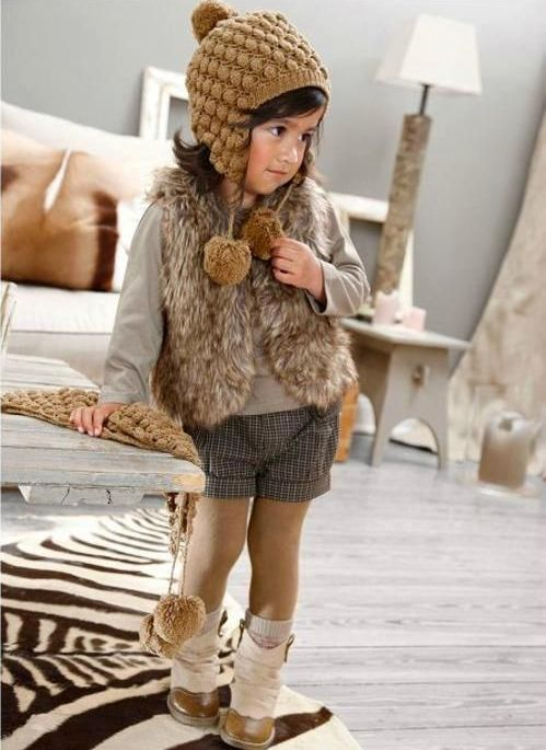 shorts, a neutral jersey, a faux fur vest and tall boots, a beanie