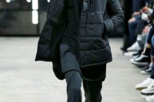 With black hat, pants, sweatshirt and mid calf boots