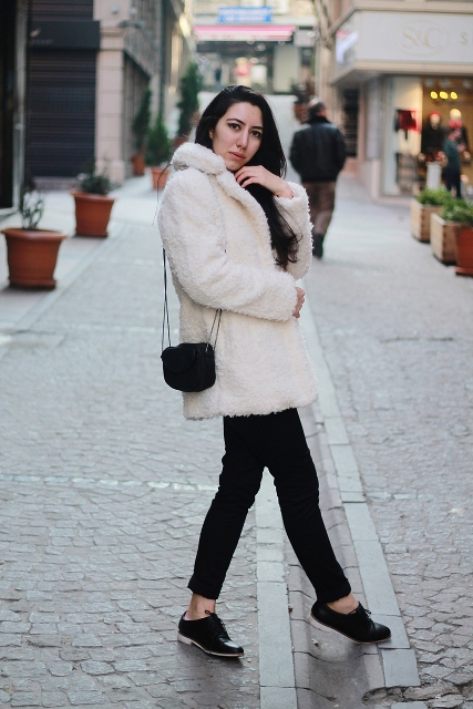 With black pants, faux fur coat and mini bag