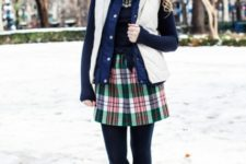 With black shirt, statement necklace, plaid skirt and vest