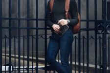 With black sweater, cuffed jeans and brown backpack