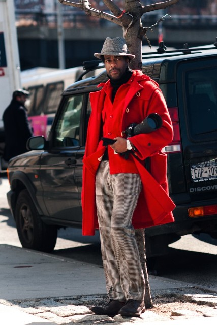 With black turtleneck, red jacket, printed trousers and hat