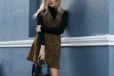 With black turtleneck, suede dress and black small bag