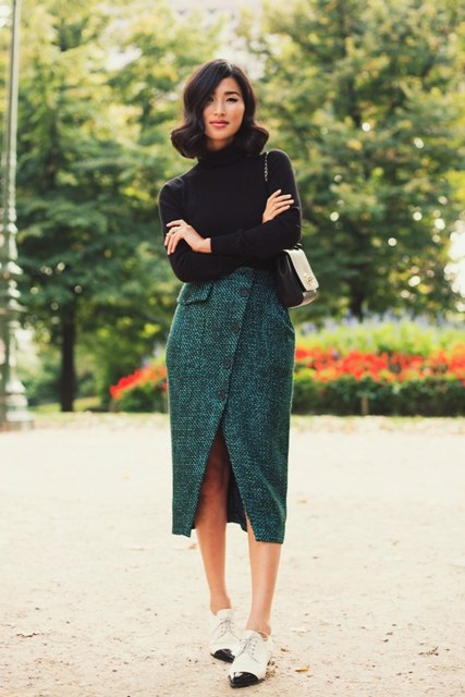 With black turtleneck, wrap skirt and mini bag