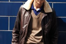 With blue shirt, brown sweater and gray pants
