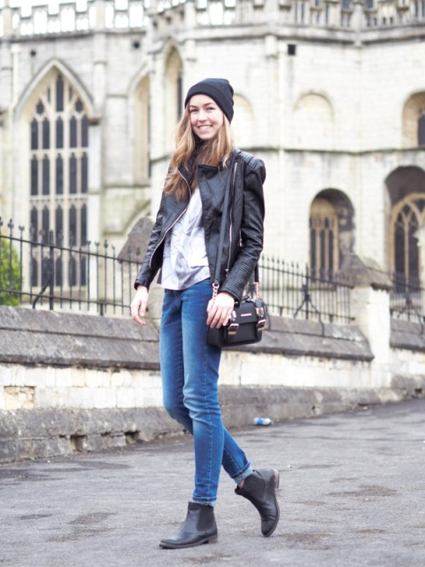 With cuffed jeans, shirt, leather jacket, beanie and mini bag