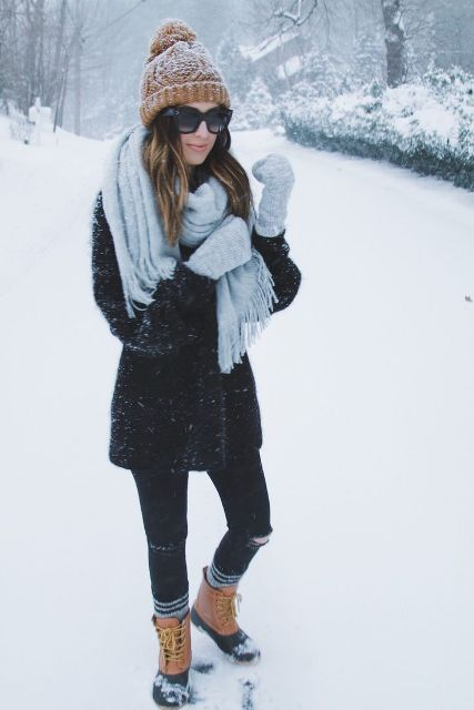 Winter outfit with a beanie, distressed skinny jeans, black coat, and an oversized scarf