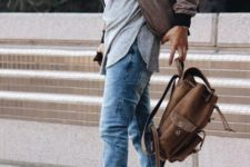With gray shirt, jacket, jeans and backpack