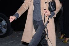 With gray turtleneck, pants, camel coat and mini bag