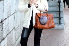 With leather pants, sneakers and brown bag