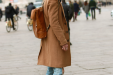 With light color jeans, white sneakers and brown backpack