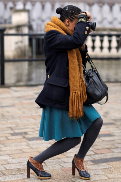 With navy blue mini coat, orange oversized scarf, skater skirt and black tights