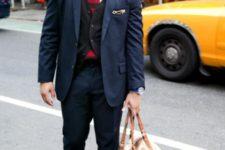 With navy blue suit, black vest, two color tie and big bag
