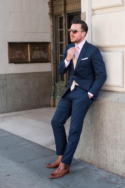 With navy blue suit, button down shirt and tie