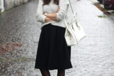 With oversized sweater, knee-length black skirt and white bag