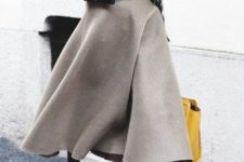 With striped shirt, leather jacket, A-line midi skirt and yellow bag