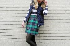 With striped shirt, plaid skirt and puffer vest